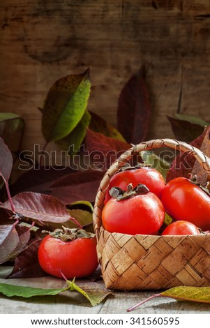 Ripe persimmons in a wicker basket on autumn background with fallen leaves on the old wooden table, selective focus - stock photo