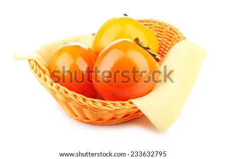 Ripe persimmons in wicker basket isolated on white - stock photo