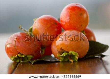 ripe persimmons on a table, outdoor - stock photo