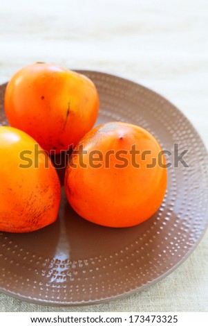 ripe persimmons on the table, food closeup