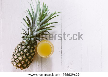 Ripe pineapple and juice glass on wooden background - stock photo
