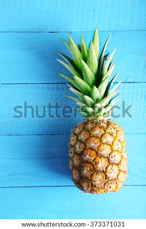 Ripe pineapple on a blue wooden table - stock photo