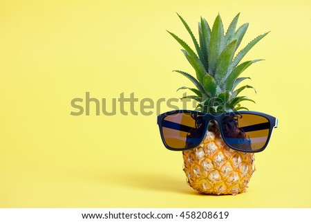 Ripe pineapple with blue sunglasses on a yellow background - stock photo