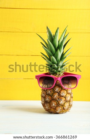 Ripe pineapple with sunglasses on a white wooden table - stock photo