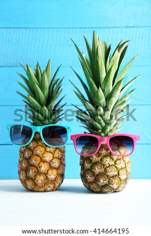 Ripe pineapples on a white wooden table - stock photo