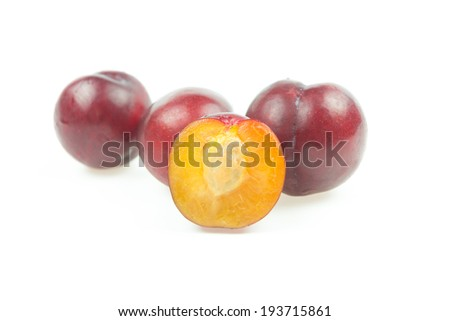 Ripe plum with slice on white background