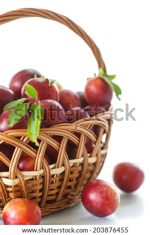 ripe plums in a basket on a white background