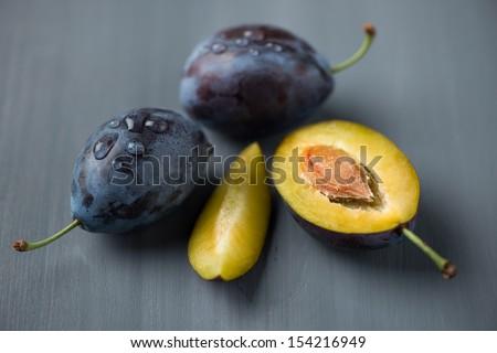 Ripe plums on grey wooden background, horizontal shot - stock photo