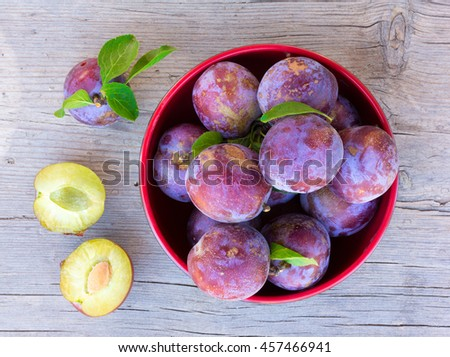 Ripe plums on old gray board close-up, top view - stock photo
