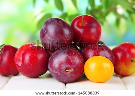 Ripe plums on wooden table on natural background - stock photo
