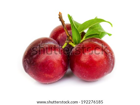 Ripe plums with leaves on white background. - stock photo