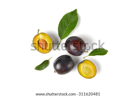ripe plums with leaves on white background - stock photo
