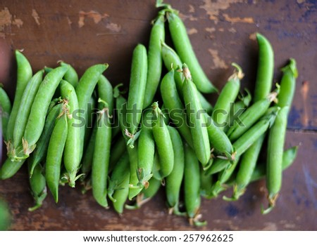 ripe pods of green peas on a  wooden table. top view - stock photo