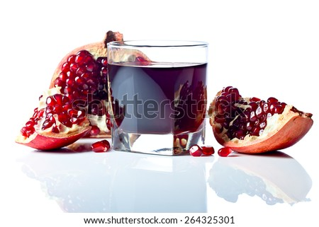 ripe pomegranate and juice isolated on a white reflexive background - stock photo