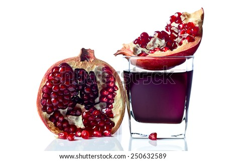 ripe pomegranate and juice isolated on a white reflexive background, focus on glass - stock photo