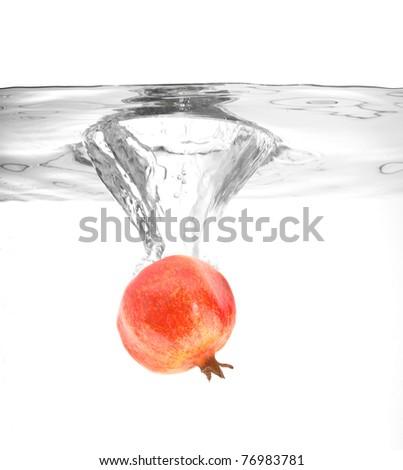 ripe pomegranate falling into water making a splash - stock photo