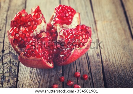 Ripe pomegranate fruit on wooden background.Toned image. Vintage style.selective focus.  - stock photo
