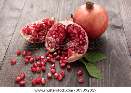 Ripe pomegranate fruit on wooden vintage table. - stock photo