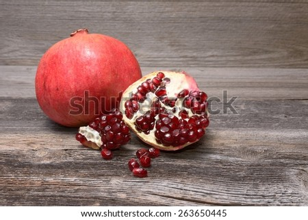 Ripe pomegranate on the wooden table. - stock photo