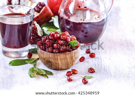 Ripe pomegranate seeds in a wooden bowl with juice on a white  vintage background. - stock photo