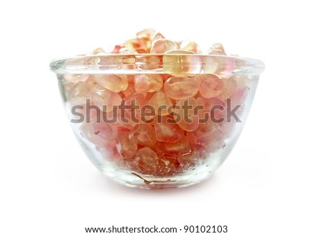 Ripe pomegranate seeds on a glass bowl isolated on white background