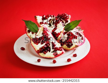 ripe pomegranate seeds on a plate on a red background.health and diet food - stock photo