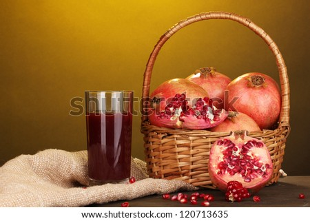 Ripe pomegranates on basket with glass of pomegranate juice on wooden table on yellow background - stock photo