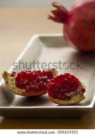 Ripe Pomegranates on decorated plate - Still Life - stock photo