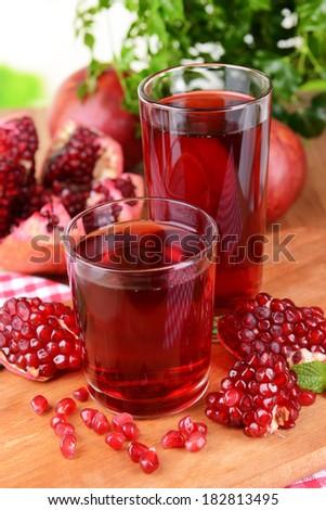 Ripe pomegranates with juice on table close-up - stock photo