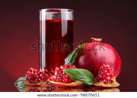 ripe pomergranate and glass of juice on red background - stock photo