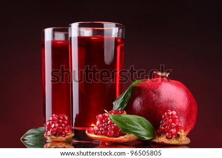 ripe pomergranate and glasses of juice on red background - stock photo