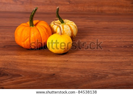 Ripe pumpkin fruits on wooden background