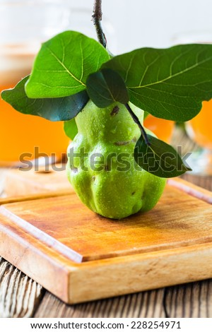Ripe quince on wooden table, and  homemade vegan fruit juice - stock photo
