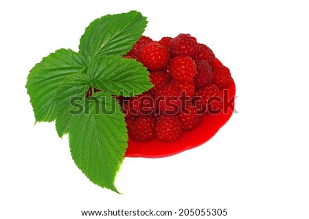 Ripe raspberries decorated with green leaf in a small platter - stock photo