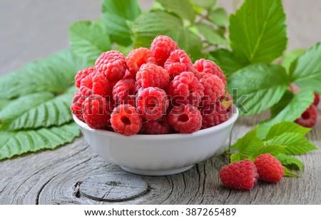 Ripe raspberries in white bowl on wooden table - stock photo