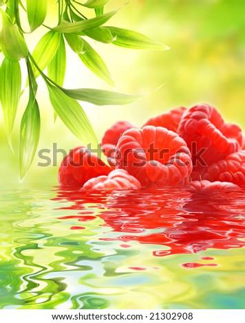 Ripe raspberries reflected in water - stock photo
