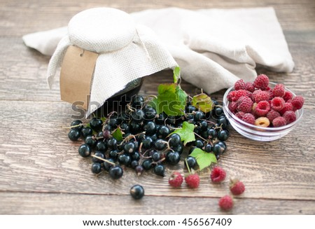 Ripe raspberry and blackcurrant on a wooden table. Food composition on a wooden background.  - stock photo