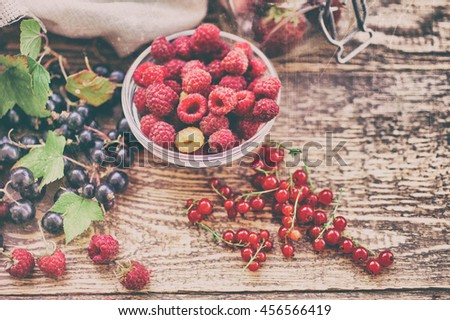 Ripe raspberry, black and red currant, strawberry on a wooden table. Vintage food composition on a wooden background. Retro toning - stock photo