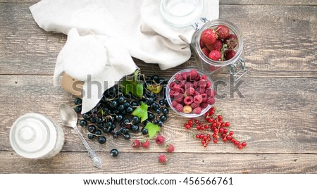 Ripe raspberry, black and red currant, strawberry on a wooden table. Vintage food composition on a wooden background. - stock photo