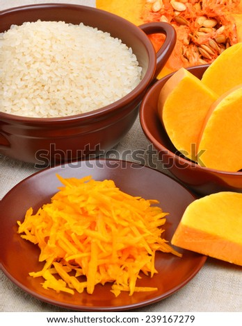 ripe raw pumpkin with grated pumpkin and uncooked rice on the ceramic brown plate - stock photo