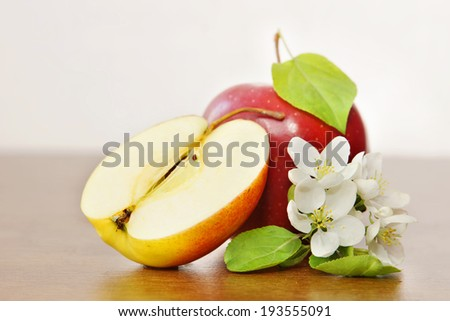 Ripe red apple fruit and apple flower on the wooden board - stock photo