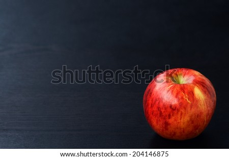 Ripe red apple on a black wooden board background with copyspace, back to school autumn theme - stock photo