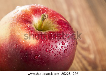 Ripe red apple on wooden table - stock photo