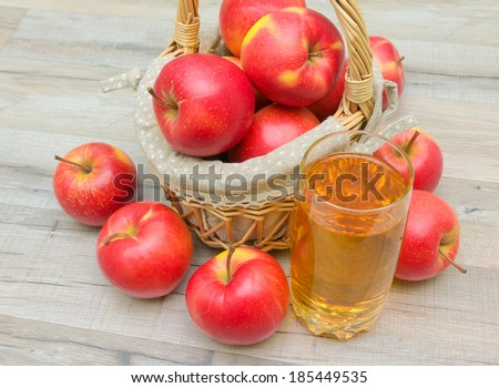 ripe red apples in a basket and a glass of apple juice. horizontal photo. - stock photo