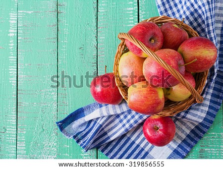 Ripe red apples in a basket on a bright wooden background. Top view - stock photo
