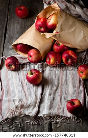 Ripe red apples in a paper bag on the table - stock photo