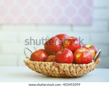 Ripe red apples in wicker basket on a kitchen table - stock photo