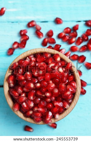 Ripe, red berry pomegranate in wooden bowl - stock photo