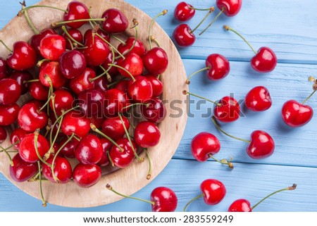 ripe, red, fresh cherries, on a blue background - stock photo