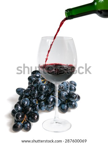 Ripe red grapes and red wine pouring from bottle into big glass isolated on white background